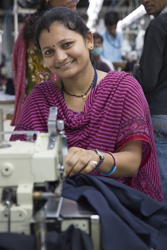"(Photo : Courtesy Fair Trade USA ) Mamta Jamri, 30-year-old tailor at Pratibha Syntex, is working at a Fair Trade Certified garment factory in India. ""I have worked here for 4 years and the workplace is so much better than before. I'm happy to contribute to the quality we produce here,"" she said, according to Fair Trade USA."
