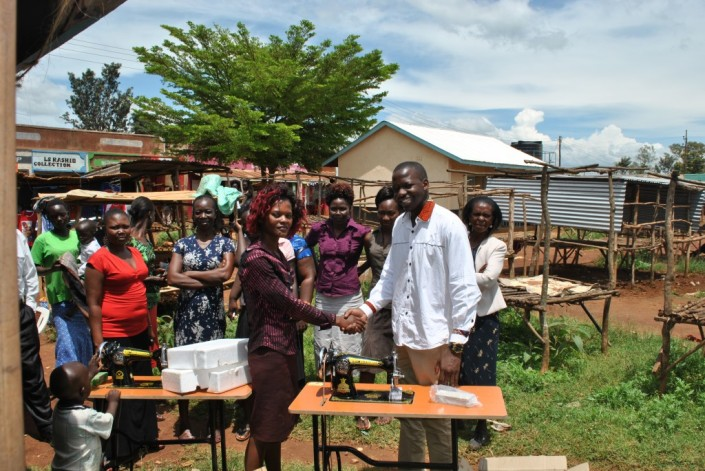 wesley-owiti-2-issuing-a-sewing-machine-to-a-beneficiary-in-ndori-market-siaya-county-1024x685